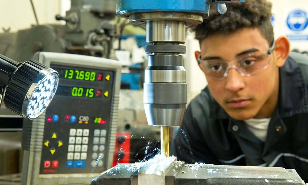 Young man working on an engineering cutting machine